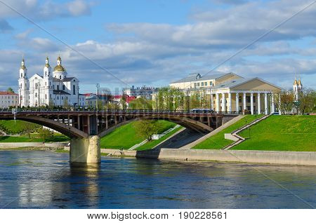 VITEBSK BELARUS - MAY 16 2017: Beautiful view of Western Dvina River Holy Dormition Cathedral and National Academic Drama Theater named after Yakub Kolas Vitebsk Belarus