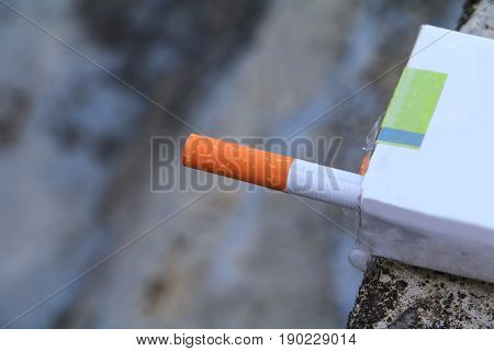 closeup cigarette in the package on cement background. concept Non-smoking day universal