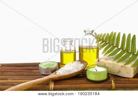 massage oil and bamboo leaf with Salt in spoon ,soap, candle on bamboo mat