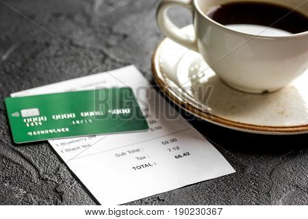 Coffee And Receipt Bill For Payment By Credit Card On Dark Table Background