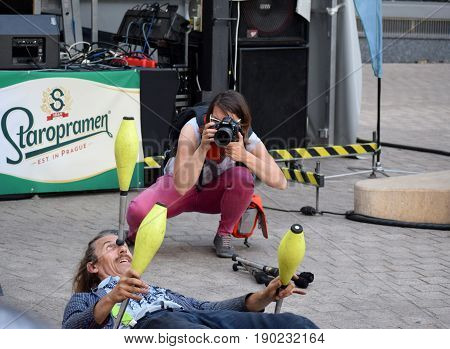 ZAGREB - MAY 2017 : Cest is d`Best famous street festival with many performers on May 2017 in Zagreb. Andy Snatch performer doing his performance play while women photographer is taking photos of him