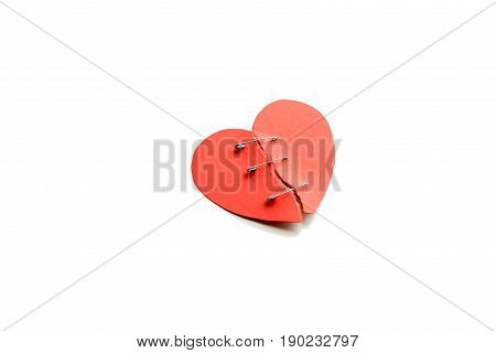 Red Heart With Broken Parts Fastened By Pins Isolated On White