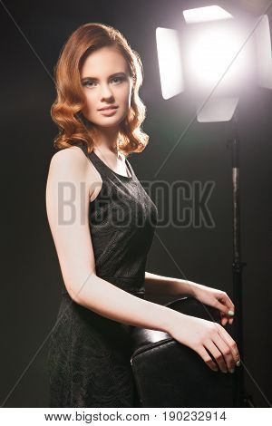 Side view of young girl in black dress leaning on leather armchair with spotlight on background