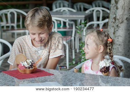 Two siblings are having fun eating their sweet Italian gelato ice cream