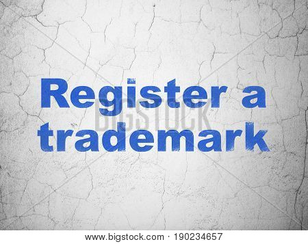 Law concept: Blue Register A Trademark on textured concrete wall background