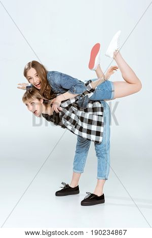 Happy Lesbian Couple Having Fun And Piggybacking Isolated On Grey