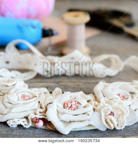 Mix materials flower necklace, glue hot gun, scissors, thread, felt on vintage wooden table. Summer beautiful fabric jewelry for women and girls. Idea of recycling fabric into stylish necklace
