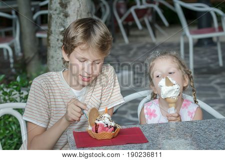 Boy and girl are eating Italian gelato in street ice cream bar