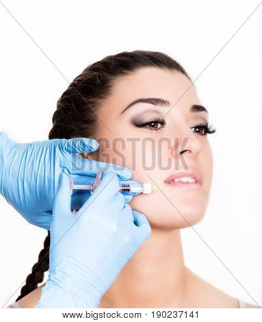 Beauty injection by doctor in blue gloves. Young woman in beauty salon. Beauty portrait. Indoor, studio