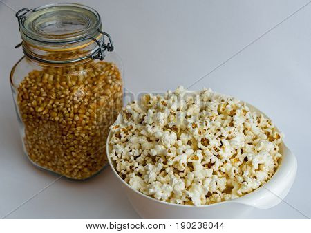 Bowl of homemade popcorn and corn seeds on white background