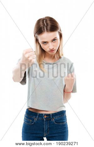 Portrait of a serious aggressive woman showing two fists isolated over white background