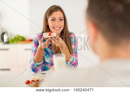 Beautiful young couple having breakfast in the domestic kitchen. Girlfriend eating sandwich and looking her boyfriend.