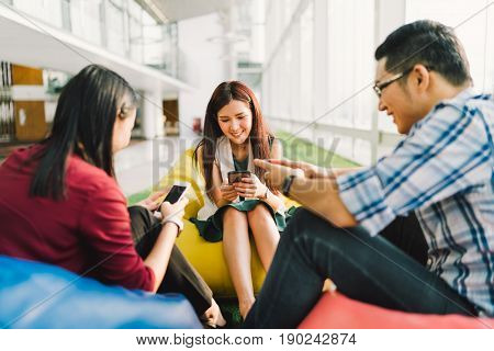 Three Asian college students or coworkers using smartphones together. Fun modern lifestyle social network or communication technology gadget concept focus on middle girl depth of field effect