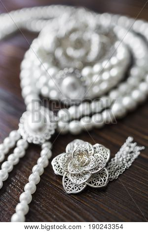 A necklace and bracelet made of white pearls with a large pearl surrounded by diamonds and a large silver brooch in the form of a flower lie on a dark brown wooden background.