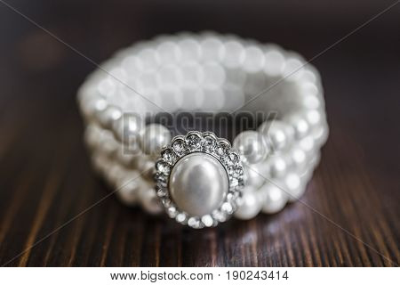 Bracelet made of white pearls with a large pearl surrounded by diamonds on a dark brown wooden background