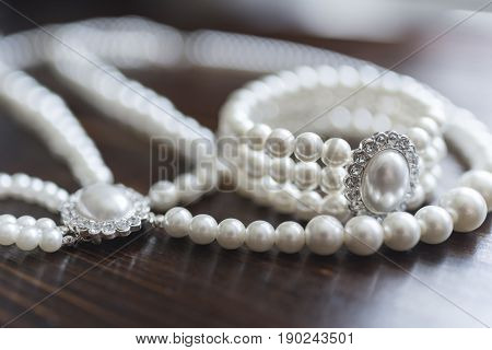 A bracelet made of white pearls with diamonds surrounded by a pearl necklace lies on a dark brown wooden background