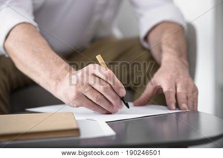 cropped image of senior businessman making notes