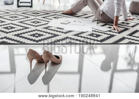 Stilettos and senior businesswoman working with documents on floor in background