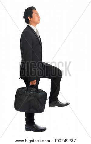 Full body attractive young Southeast Asian businessman stepping up stair case, isolated on white background. Asian malay male model.