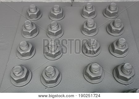 Painted gray bolts with thread with screwed nuts on the metal panel.