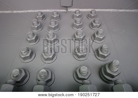 Gray bolts with thread with screwed nuts on the metal panel.