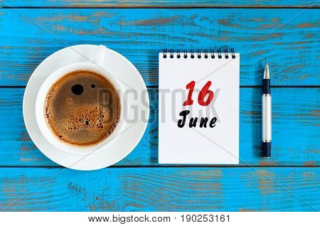 June 16th. Image of june 16 , daily calendar on blue background with morning coffee cup. Summer day, Top view.