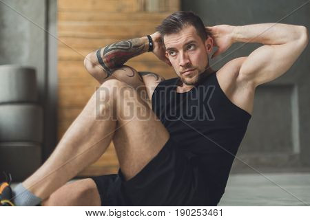 Young man workout in fitness club. Portrait of caucasian guy making exercise, sit-ups and cross crunches for abs muscles, training indoors