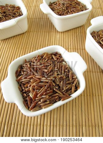 Uncoocked red camargue rice in white bowls