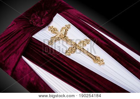 closed red velvet coffin covered with cloth isolated on gray background. coffin close-up with gold Church cross on royal background. Ritual objects for burial. Surrender body dust of the earth. Christian funeral ritual