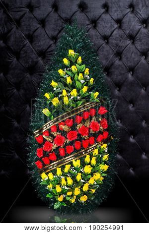 Luxury Funeral wreath with red and yellow flowers isolated on royal dark background. Ritual object for funeral