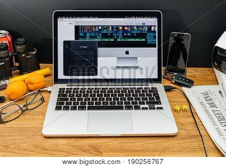 PARIS FRANCE - JUNE 6 2017: Apple Computers website on MacBook Retina in creative environment showcasing latest news from Apple at WWDC 2017 - Promise pegasus thunderbolt dock nas next to imac