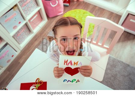 girl surprising parents with greeting card at home