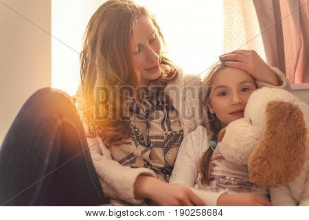 mother giving daughter solace while illness