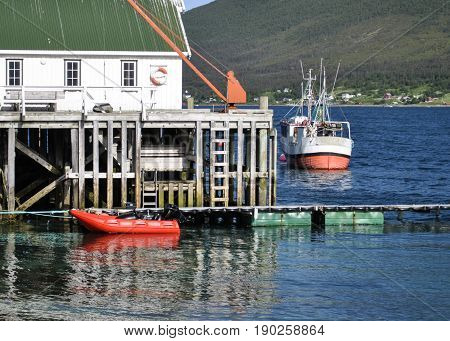 Two fishing boats on the dock in the fjord.