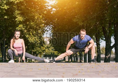 Fit fitness woman and man doing stretching exercises outdoors at park. Couple doing hamstring leg stretching exercise and stretches. Female amd male sports models exercising outdoor in summer.