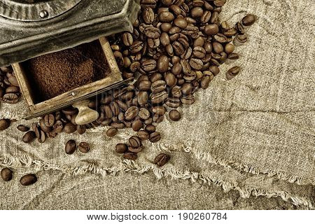 Coffee Grinder And Coffee Beans On Burlap Fabric