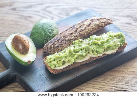 Sandwich with smashed avocado on the wooden board