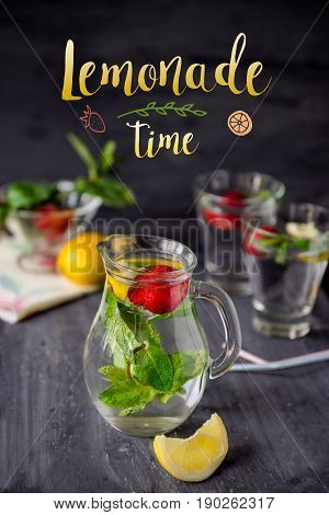 Card with bright phrase Lemonade time and Flavored water with fresh strawberries and mint in glass jars on a black wooden table with details.Selective focus close up
