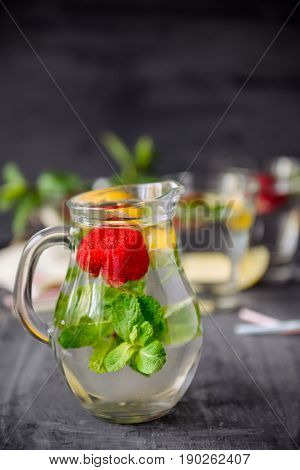 Flavored Water With Fresh Strawberries And Mint In Glass Jars On A Black Wooden Table With Bright De