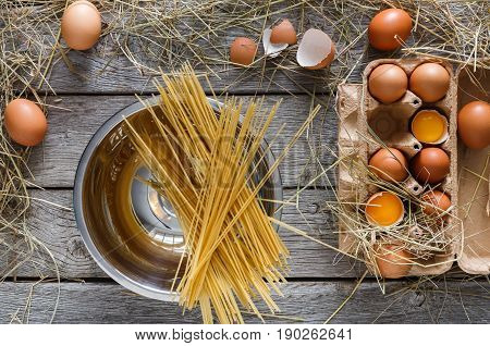 Cooking background. Raw Vermicelli in pot and fresh chicken eggs in carton, top view on rustic wood background