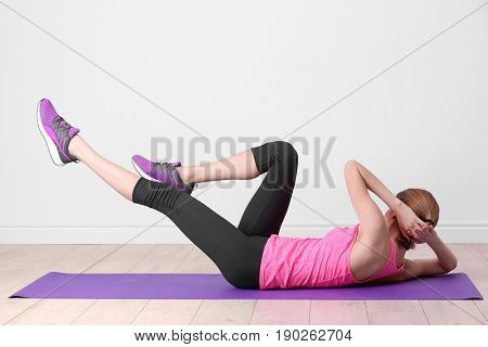 Beautiful woman doing bicycle crunch on light wall background