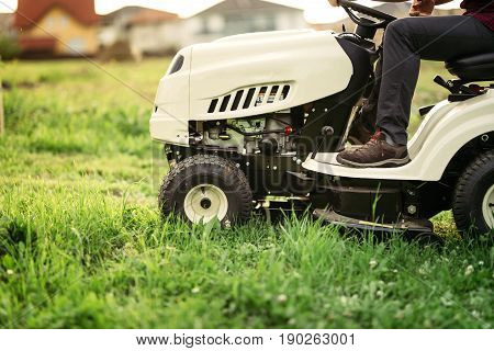 Gardner On Mower Doing Landscaping Works And Cutting Grass. Professional Worker Mowing Lawn