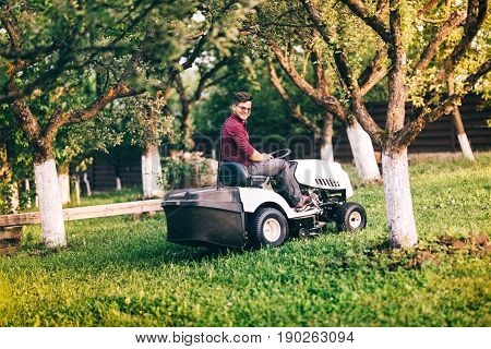 Smiling Gardner Working And Cutting Grass In Garden. Detail Of Landscaping Works With Lawnmower