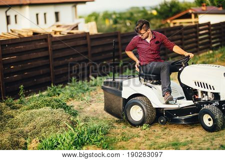 Man With Lawn Mower, Professional Worker Cutting And Unloading Grass