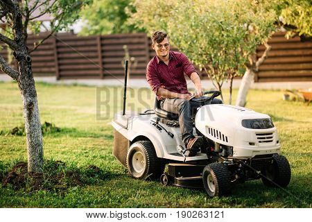 Male Worker Using Lawmower For Landscaping Works. Motorised Agriculture Concept