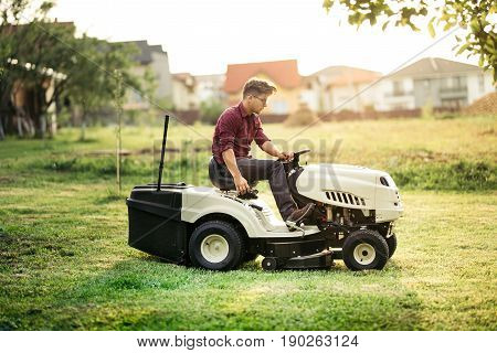 Professional Gardner mowing lawn with ride-on tractor