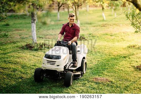 Man Using Ride On Lawnmower, Male Riding Lawn Tractor And Relaxing During Sunset Golden Hour