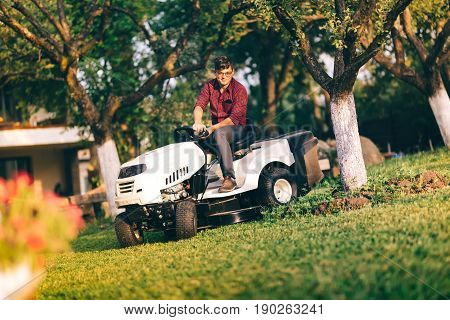 Lawncare Concept - Handsome Young Man Trimming Grass In Garden Using Tractor