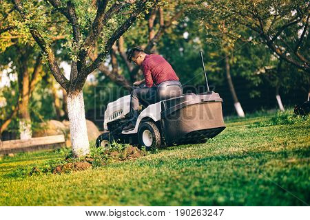 Male Worker Carefully Trimming Lawn. Grass Cutter Occupation In Industrial Field