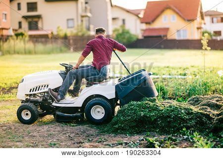 Man With Lawn Tractor Unloading Cut Grass During Landscaping Works